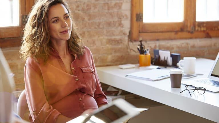 Pregnant businesswoman sitting at desk