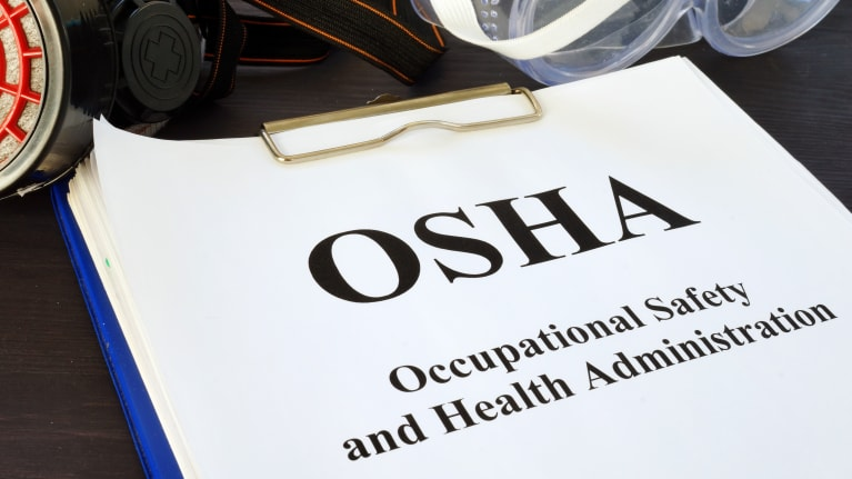 Clipboard with Occupational Safety and Health Administration paperwork on it