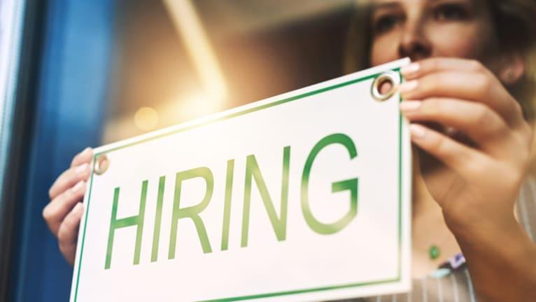 woman hanging hiring sign