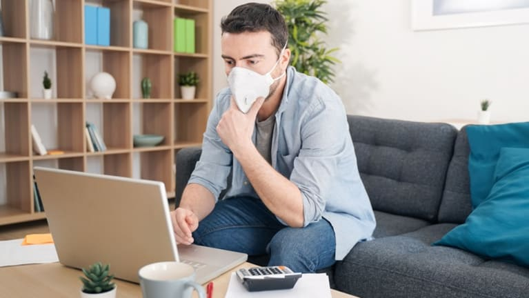 employee wearing face mask selects benefits from his laptop.