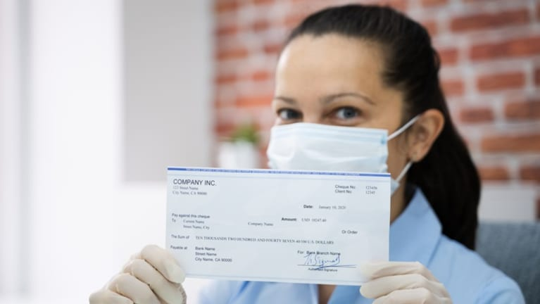 open paycheck wearing surgical mask during pandemic