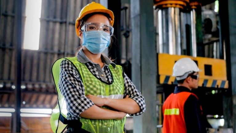 Woman wearing pandemic mask, managing warehouse workers.