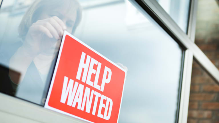 woman hanging help wanted sign