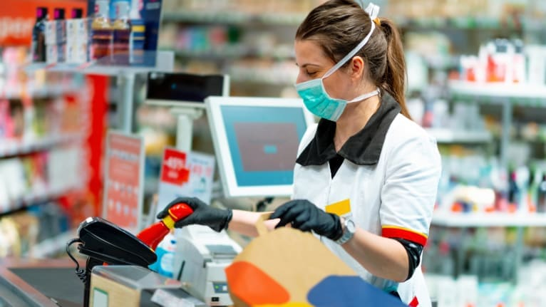 a check-out clerk wearing a mask and gloves