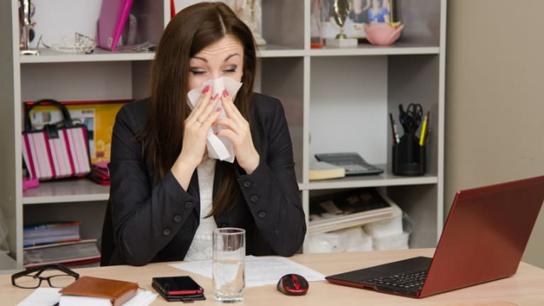 woman sneezing at office desk