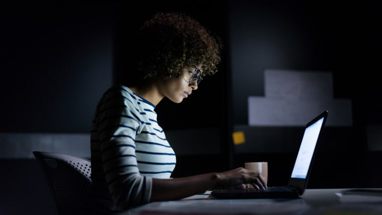 women working at desk at night