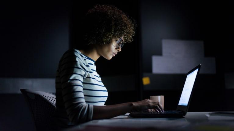 women working on laptop at night