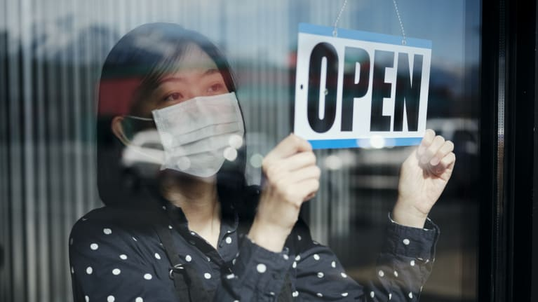Business Owner with Open Sign Wearing Mask