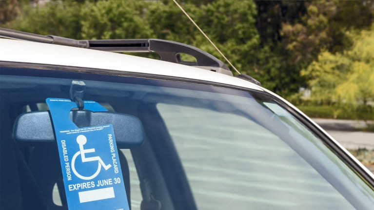 disabled parking placard hanging from a car windshield