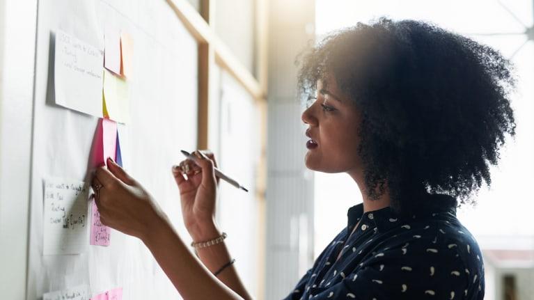 women working out schedule on bulletin board