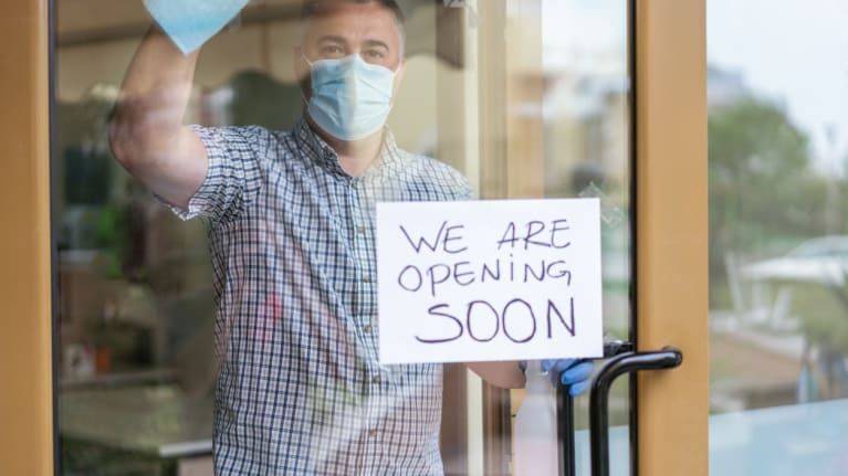 """shop owner with """"opening soon"""" sign"""