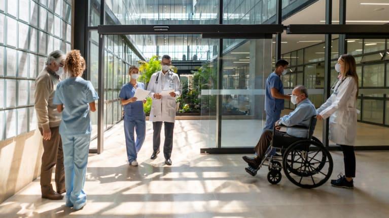 People walking around hospital wearing masks