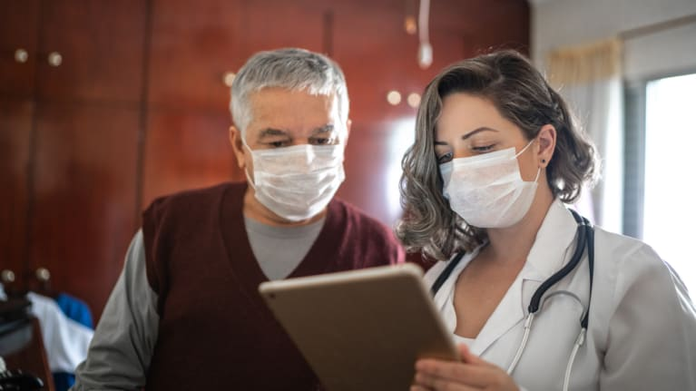 Health worker and patient wearing masks