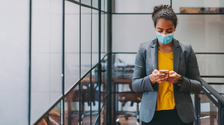 business woman in face mask checks phone