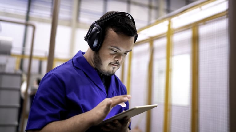 employee with earphones on using a tablet