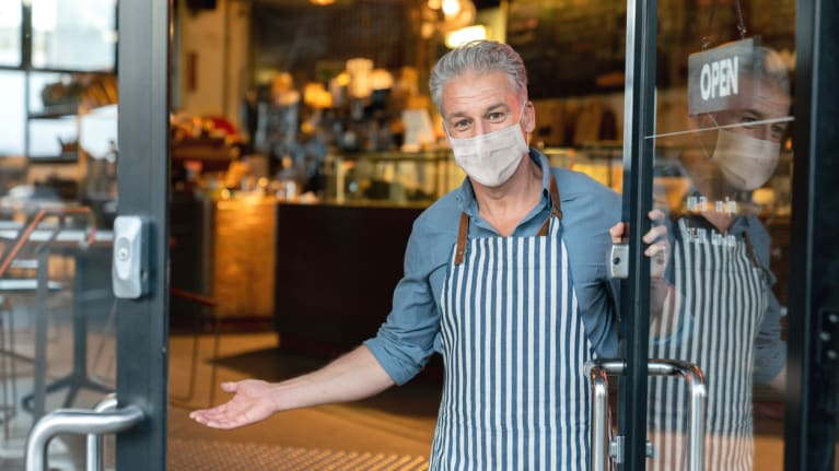 Business owner wearing a facemask and reopening his cafe