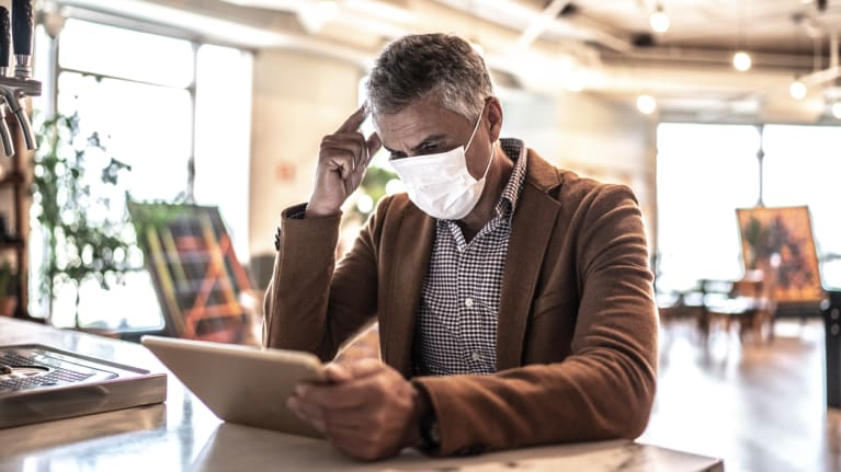 man wearing mask working on laptop