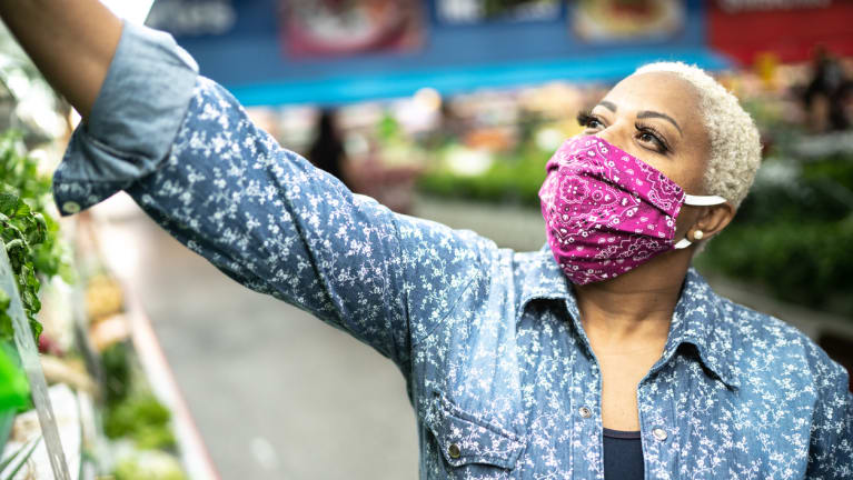 masked grocery store customer reaching for food