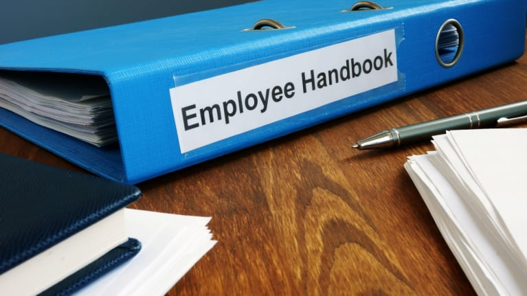 an employee handbook near two pens and a stack of papers