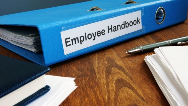 an employee handbook and pen