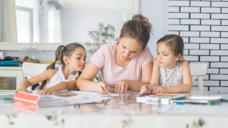 woman doing school work with children at home