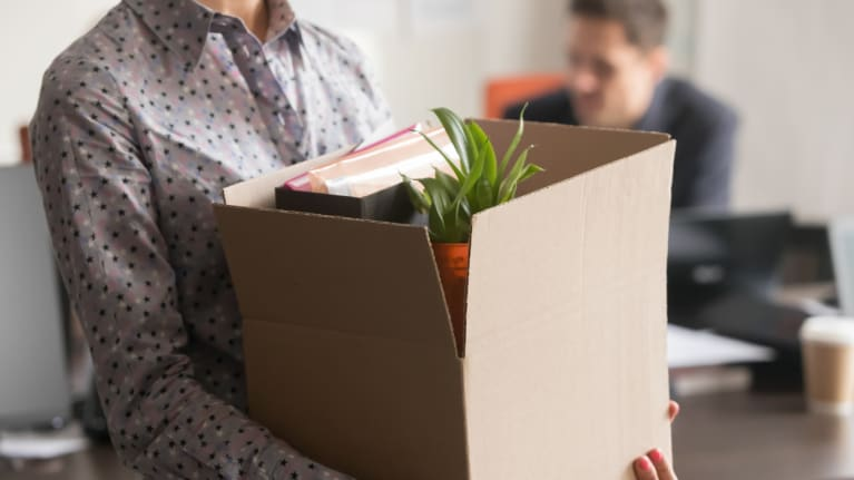 laid-off worker carrying personal items home in a box