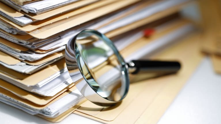 a magnifying glass resting on a stack of folders