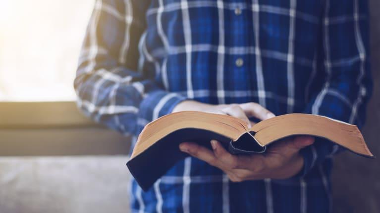 man holding religious book