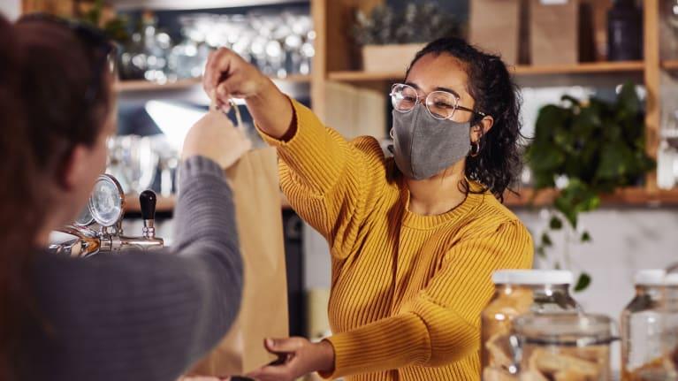 cafe worker wearing a amsk handing customer a bag
