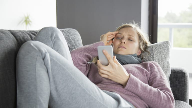 sick woman lying on couch looking at cell phone