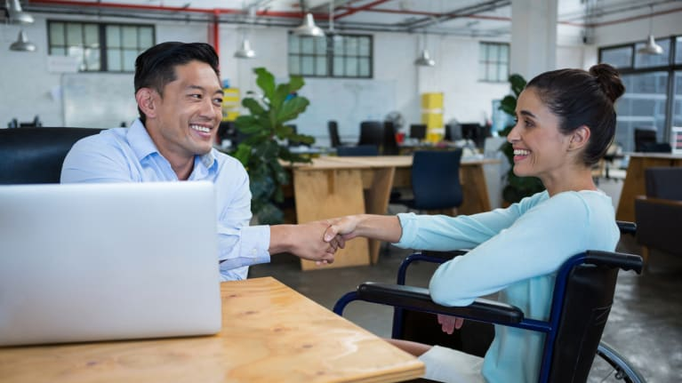 interviewer shaking hands with job applicant who is a wheelchair user