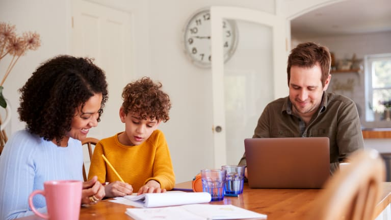 Parents and child working at kitchen table