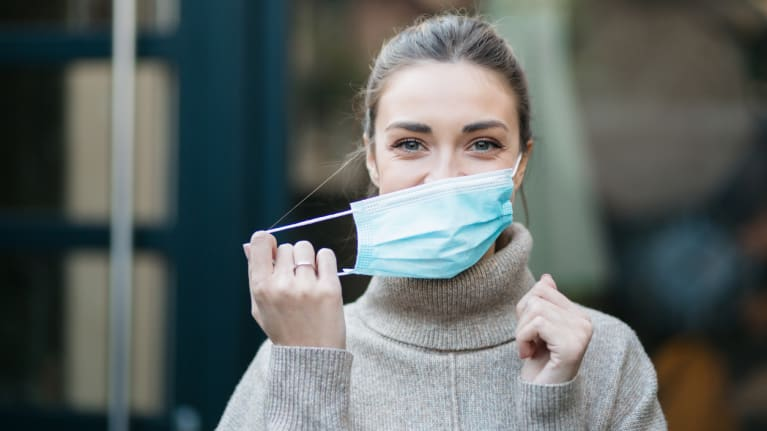 woman taking off a protective face mask