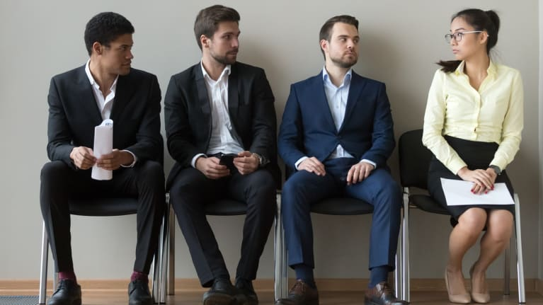 three men and one woman await job interview