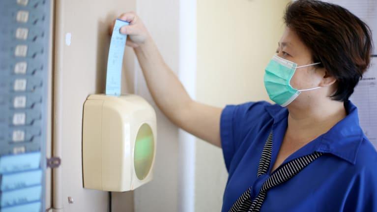 worker clocking in wearing mask