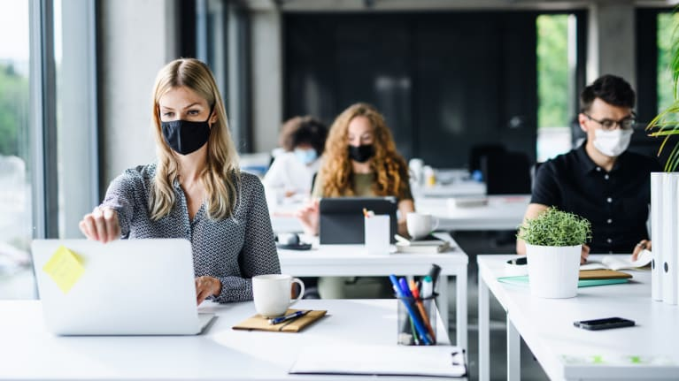 office workers wearing masks and distancing