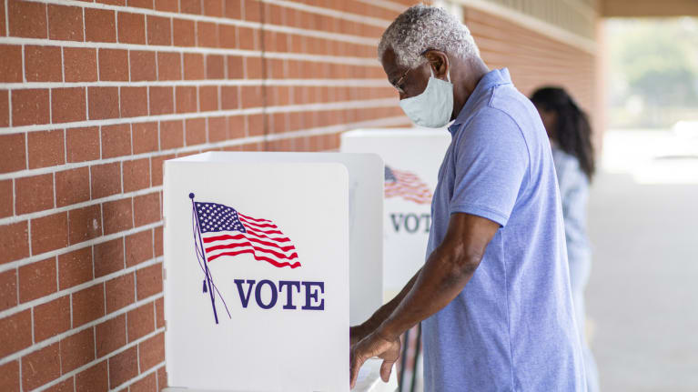Man Voting with a Mask On