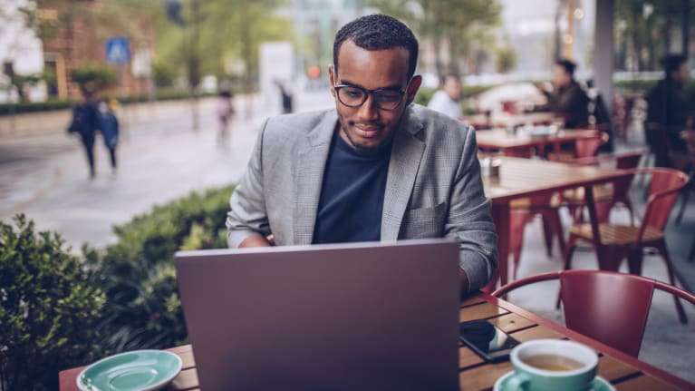 man sitting in coffee shop and using laptop