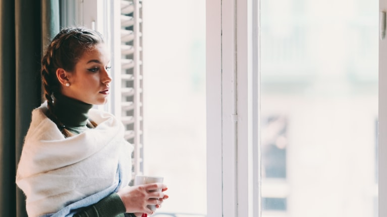 Woman in quarantine looking out window and drinking tea