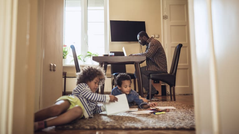 dad working from home as kids play on the floor
