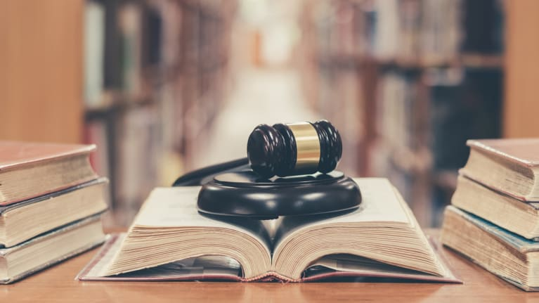 a gavel on an open lawbook in a library