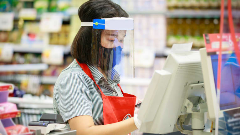 supermarket staff in protective mask and face shield