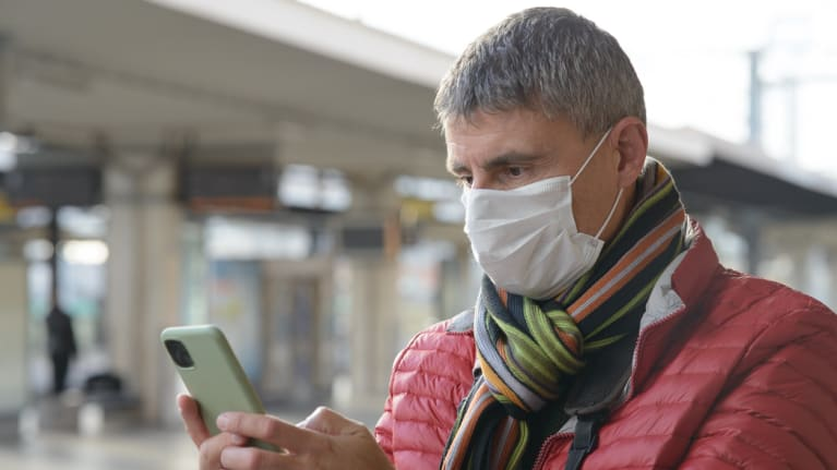 man wearing mask gets text alert