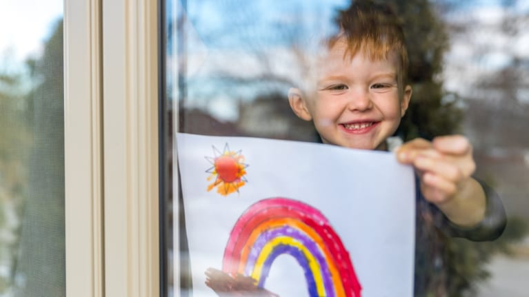 child hangs rainbow picture in window