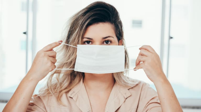 woman holding surgical mask