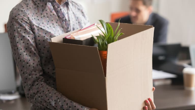 A terminated employee carrying a box of personal items out of the office
