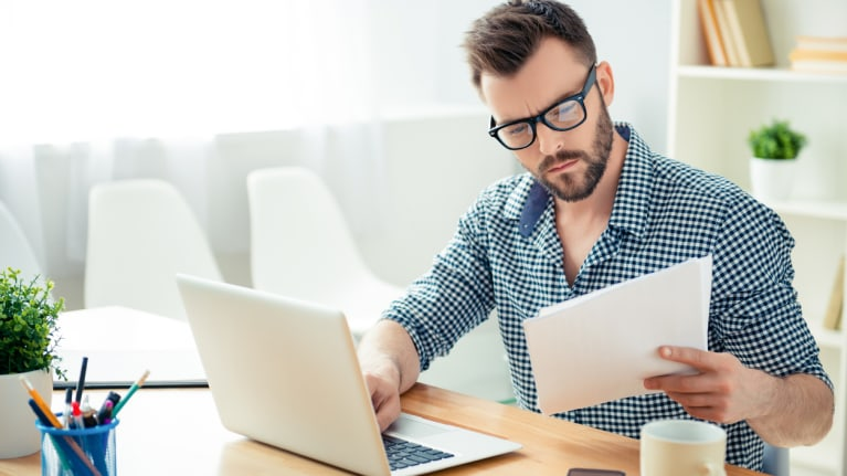 man reviewing paperwork and on computer