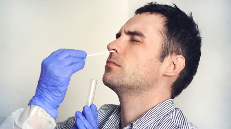 a man getting his nose swabbed in a COVID 19 test