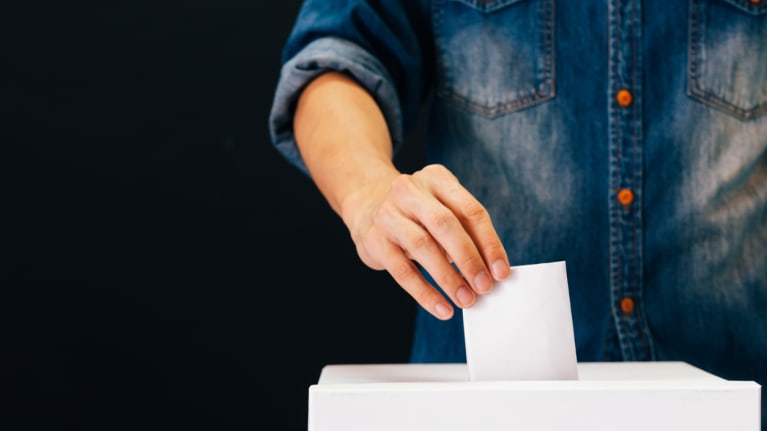 voter putting ballot in ballot box
