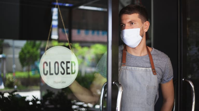 restaurant worker wearing mask hanging up sign closed